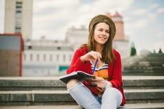 Piękny, młody Kaukaski dziewczyny obsiadanie na ulicznym uśmiechu radość, siedzi z notatnikiem i pisze w Ruhi W czerwonym pulower Obraz Stock