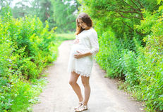 Piękny młody kobieta w ciąży w biel sukni na naturze Zdjęcia Royalty Free