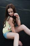 Piękny młody modniś dziewczyny obsiadanie po środku asfaltu ro Obrazy Stock