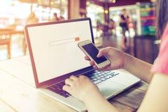 piękny młody modniś kobiety ` s wręcza ruchliwie działanie na jej laptopie, kobieta używa komórka telefonu obsiadanie przy drewni Zdjęcia Stock