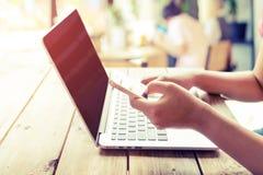 Piękny młody modniś kobiety ` s wręcza ruchliwie działanie na jej laptopie, kobieta używa komórka telefonu obsiadanie przy drewni Fotografia Stock