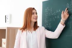 Piękny młody nauczyciel wyjaśnia matematyk formuły zdjęcie royalty free