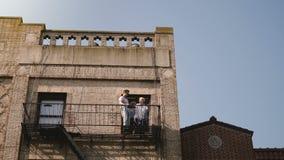 Piękny młody romantyczny pary przybycie z mieszkania okno mały balkon stary budynek w ranku Nowy Jork zbiory wideo