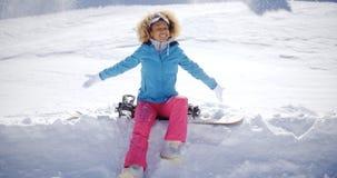 Piękny młody snowboarder obsiadanie na śniegu Zdjęcia Stock