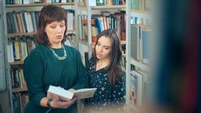Piękny młody uczeń i nauczyciel dyskutuje w bibliotece zbiory wideo
