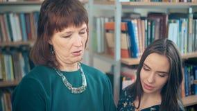 Piękny młody uczeń i nauczyciel dyskutuje w bibliotece zdjęcie wideo