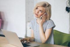 Piękny młody uczeń siedzi przed laptopem i mówi na telefonie Zdjęcie Stock