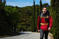 Piękny młody wycieczkowicz z plecaka odprowadzeniem na opustoszałej drodze i ono uśmiecha się w górach Obrazy Royalty Free