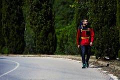 Piękny młody wycieczkowicz z plecaka odprowadzeniem na opustoszałej drodze na pięknym drzewa tle Obrazy Stock
