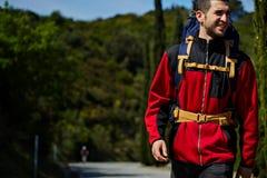 Piękny młody wycieczkowicz z plecakiem iść na opustoszałej drodze i ono uśmiecha się w górach Obrazy Royalty Free