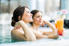 Piękny młodych kobiet pić koktajle w pływackim basenie Obraz Royalty Free