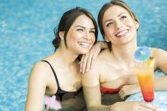 Piękny młodych kobiet pić koktajle w pływackim basenie Obrazy Stock