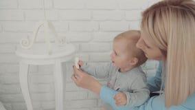 Piękny mała dziewczynka pobyt blisko lampy z matką i stołu swobodny ruch Dziecko kamień milowy, berbeć, 1 roczniak Szczęśliwy zbiory wideo