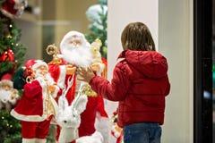 Piękny małe dziecko, chłopiec, ogląda Bożenarodzeniową dekorację z zabawkami w sklepowym nadokiennym pokazie, życzy dla teraźniej fotografia stock
