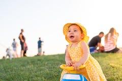 Piękny małe dziecko dziewczyny obsiadanie na zabawkarskim samochodzie outdoors obrazy stock