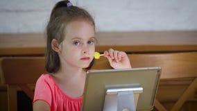 Piękny małej dziewczynki łasowania lody i dopatrywanie kreskówka na pastylce zbiory