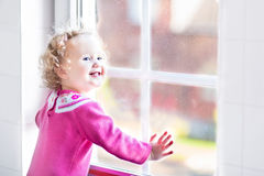 Piękny małej dziewczynki dopatrywanie z okno obraz stock