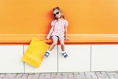 Piękny małej dziewczynki dziecko będący ubranym okulary przeciwsłonecznych z torba na zakupy chodzi w mieście nad kolorową pomara Zdjęcia Royalty Free