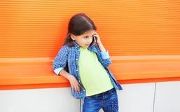 Piękny małej dziewczynki dziecko opowiada na smartphone w mieście Zdjęcia Royalty Free