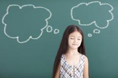 Piękny małej dziewczynki główkowanie przed chalkboard obraz royalty free