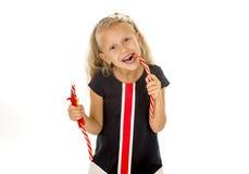 Piękny mały żeński dziecko je truskawkowego lukrecjowego cukierek z niebieskimi oczami Zdjęcia Royalty Free