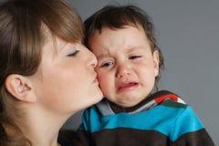 Piękny macierzysty całowanie jej płaczu syn obrazy royalty free