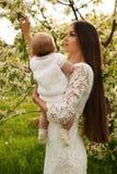 Piękny macierzysty pozować z jej małym ślicznym dzieckiem w okwitnięcie ogródzie Zdjęcia Stock