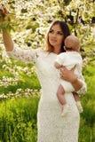 Piękny macierzysty pozować z jej małym ślicznym dzieckiem w okwitnięcie ogródzie Fotografia Royalty Free