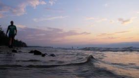 Piękny magiczny zmierzch na dennym wybrzeżu wzdłuż którego iść mężczyzna zbiory