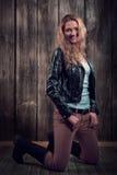 Piękny moda model z blond kędzierzawym włosy jest ubranym czarną kurtkę, spodnia i czarnych wysokich buty w pozie na jej kolanach, Obraz Royalty Free