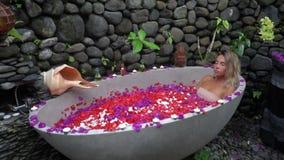Piękny model kłama w wodzie w plenerowej wannie folującej z różami Zdroju jard taflujący z kamieniem i pięknie dekorujący zbiory wideo