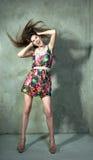 Piękny model w jaskrawej kolor sukni pozuje trzymający jej głowę zdjęcia royalty free