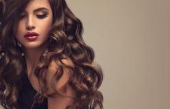 Piękny model z długą, zwartą i kędzierzawą fryzurą, obraz stock