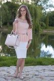 Piękny model z długim kędzierzawym włosy trzyma torebkę na jaskrawym Zdjęcia Stock