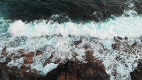 Piękny morze macha splashiung przeciw skalistej plaży Zamyka w górę trutnia strzału zbiory wideo