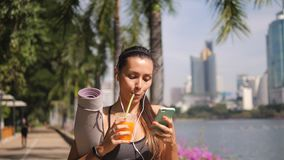 Piękny napad Mieszająca Biegowa kobieta Używa telefon komórkowego App i Pijący Świeżego sok pomarańczowego po ranku joga praktyki zdjęcie wideo