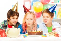 Piękny nastoletni dziewczyna ciosu tort na przyjęciu urodzinowym Zdjęcia Royalty Free