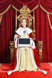 Piękny nastoletni dziewczyny mienia laptop podczas gdy siedzący w rocznika karle obrazy stock
