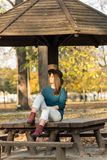 Piękny nastoletniej dziewczyny obsiadanie na parkowej ławce z czarnego kapeluszu błękitnym pulowerem i rozdzierającymi cajgami z  Zdjęcia Royalty Free