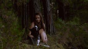 Piękny naturalny dziewczyny obsiadanie w lesie z jej psim patrzeje dobrem w jego ono przygląda się zbiory