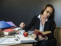 Piękny nauczyciela obsiadanie przy jej biurka czytaniem obraz royalty free
