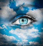 Piękny niebieskie oko przeciw błękitowi chmurnieje - Duchowego pojęcie fotografia royalty free