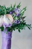 Piękny nieociosany ślubny bukiet fiołkowa i biała ranunculus lawenda kwitnie z atłasową lilą taśmą na bielu obraz royalty free