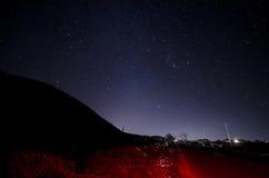 Piękny noc krajobraz gwiazdy przy nieba i góry sylwetką blisko drogi z samochodowymi śladami Droga w górach pod gwiaździstym obrazy stock
