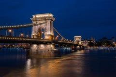 Piękny noc strzał iluminujący Łańcuszkowy most w Budapest przez Danube rzekę w Węgry Zdjęcia Royalty Free