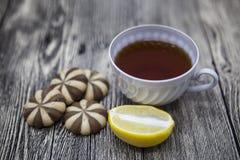 Piękny opanowany na drewnianej tło filiżance herbaciana cytryna i ciastka zdjęcia royalty free