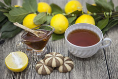 Piękny opanowany na drewnianej tło filiżance herbaciana cytryna i ciastka obrazy stock