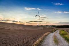 Piękny półmrok przy polem z silnikiem wiatrowym w jesieni obrazy stock