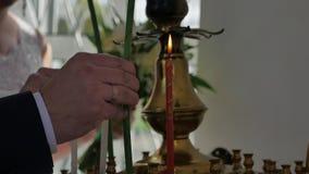 Piękny państwo młodzi trzyma świeczki podczas ślubnej ceremonii w kościół, wspaniałej blondynki pannie młodej i przystojnym forna zbiory wideo