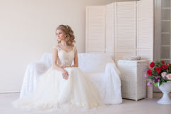 Piękny panny młodej obsiadanie na białej leżance w ślubnej sukni Zdjęcie Royalty Free